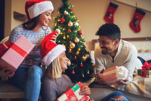 自宅でクリスマス休暇を楽しんでいる間、プレゼントを持ち、寝室でジョークを話しているセーターでサンタ帽子をかぶった3人のうれしそうなスタイリッシュな友人。