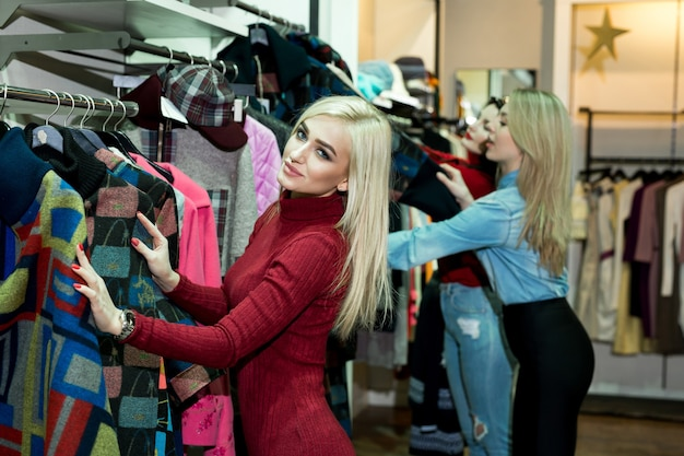 의류 매장에서 따뜻한 재킷을 쇼핑하는 세 즐거운 젊은 여성.