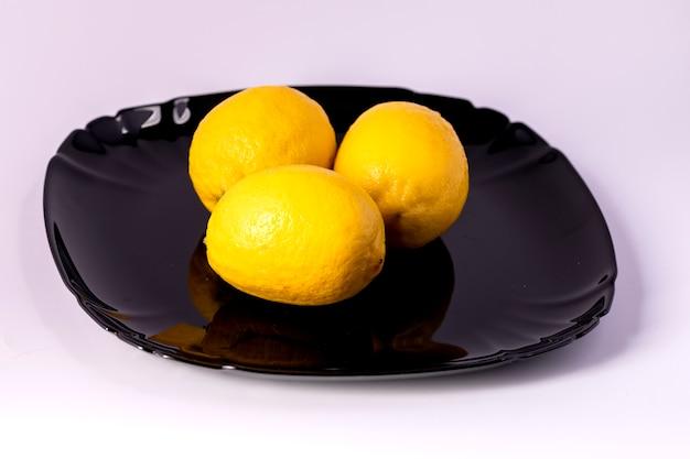 흰색 배경에 검정 잉크 판에 세 육즙 신선한 노란색 레몬.