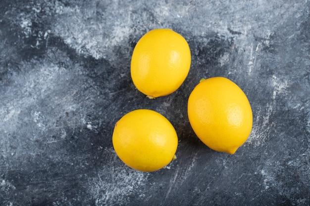 Three juicy ripe lemons placed marble surface