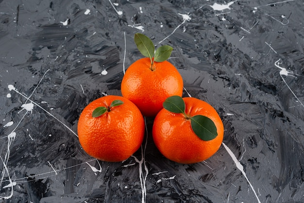 Three juicy tangerine fruits with leaves on marble surface.