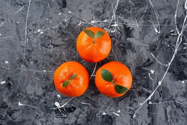 Tre succosi frutti di mandarino con foglie sulla superficie in marmo.