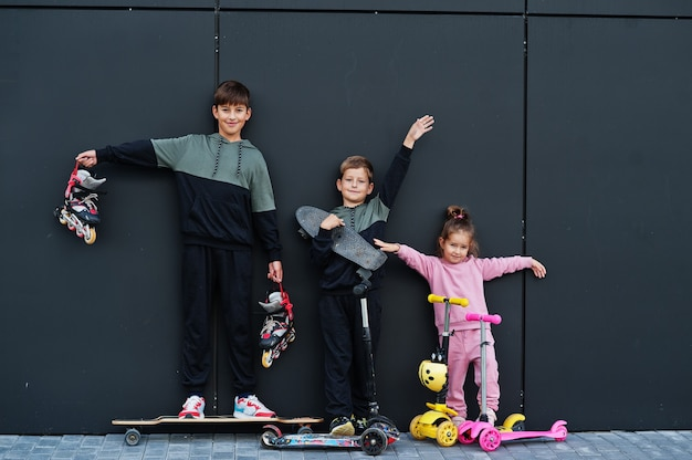 黒のモダンな壁に対して屋外の3人の子供。スポーツの家族は、スクーターやスケートで屋外で自由な時間を過ごします。