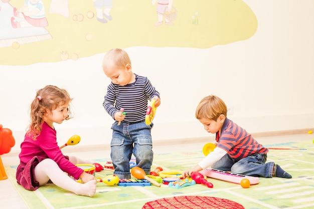 놀이방에서 노는 세 아이. 아이들은 자신이 음악가라고 상상합니다. 소녀는 드럼을 연주하고, 첫 번째 소년은 실로폰을 연주하고, 두 번째 소년은 피아노를 연주합니다.