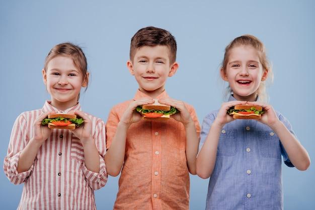 サンドイッチを持つ3人の子供は、青い背景のコピースペースで隔離のカメラを見てください