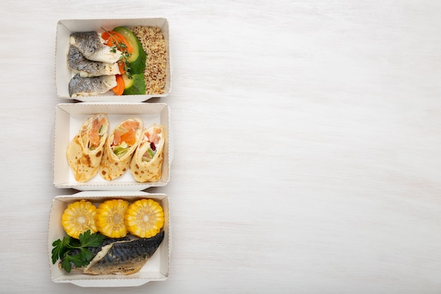 Three kinds of lunch boxes with fish and vegetables lie on a white table. space for advertising