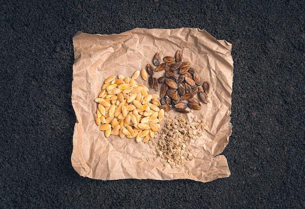 Три вида семян крупным планом в крафт-бумаге на земле. тыквенные семечки, арбуз и помидор. вид сверху, горизонтальный.