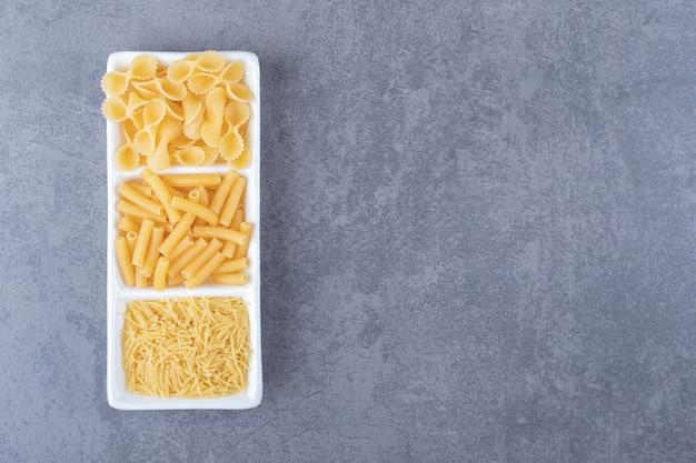 Tre tipi di pasta cruda sul piatto bianco.