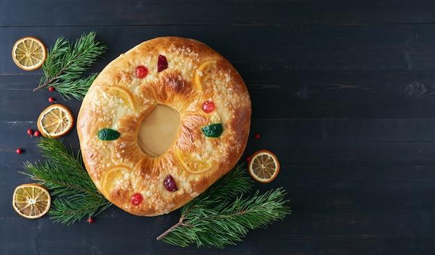 Торт трех королей с рождественским украшением на темном деревянном столе.