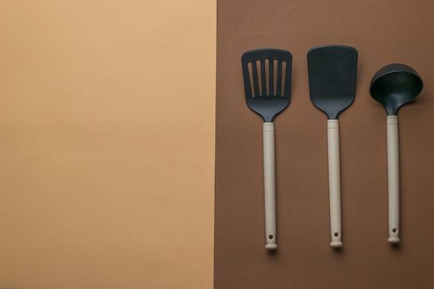 Три кухонные шпатели на двухцветном фоне. место для текста. пластиковые кухонные инструменты. плоская планировка.