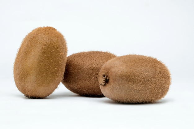Three kiwi fruits on a white surface