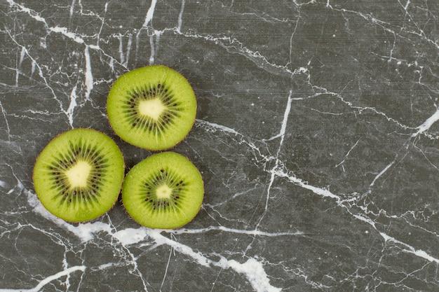 Three kiwi slice on black stone.
