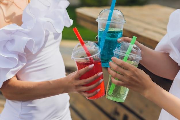 Три дамы ликуют вкусными нектарами с кубиками льда с черной соломкой украшение ладоней в бассейне прозрачная чистая чистая голубая вода солнце светит гладкой загорелой кожей беззаботный праздничный режим
