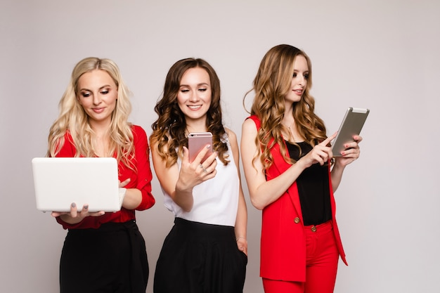 Три дамы с помощью гаджетов три великолепные элегантные молодые женщины в повседневной одежде