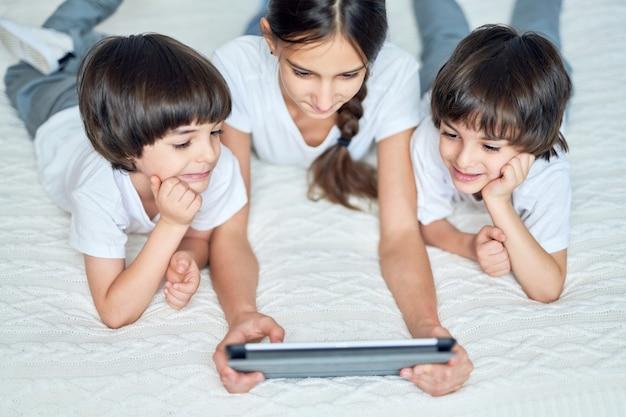 집에서 침대에 누워 디지털 태블릿을 사용하는 동안 쾌활해 보이는 세 라틴 어린이. 십대 자매는 만화를 보면서 두 명의 남동생을 즐겁게 합니다. 행복한 어린 시절, 기술 개념