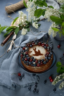 Three layers bird cherry cake with sour cream decorated with fresh berries and cherries