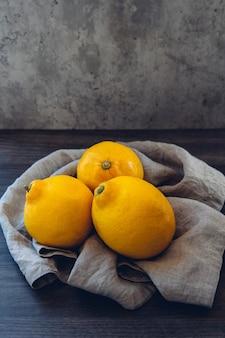 나무 테이블에 레몬 세 개와 배경에 민트 잎