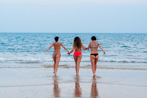 Three lesbian girlfriend girls running on the beach in the sea back