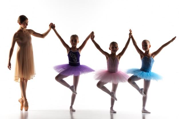 Три маленькие балерины танцуют с личным учителем балета в танцевальной студии