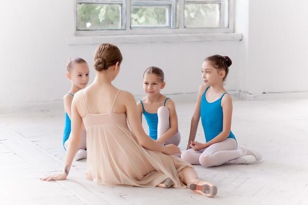 댄스 스튜디오에서 개인 발레 선생님과 함께 춤추는 세 명의 작은 발레리나