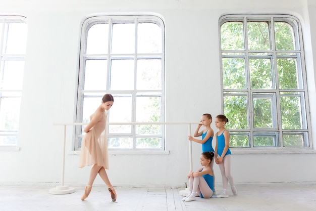 Three little ballerinas with personal ballet teacher in dance studio. classic ballet dancer  as teacher posing on one leg at ballet barre in a white studio