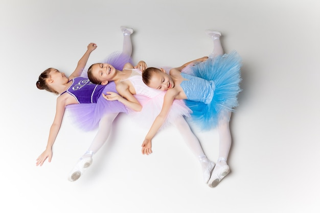 Three little ballet girls lying in ballet stretch in multicolored tutu and pointe shoes