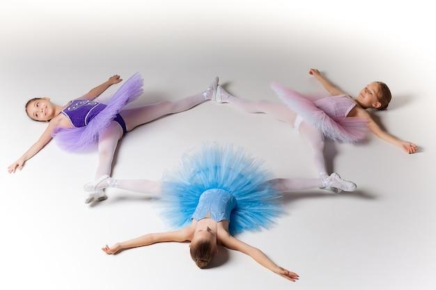 Три маленькие балетные девочки, лежащие в балетной тяге в разноцветной пачке и пуантах вместе на белом фоне