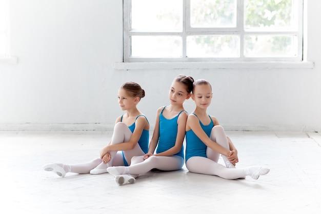 一緒に座ってポーズをとる3人の小さなバレエの女の子