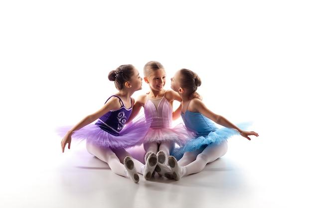 白い背景の上に一緒に色とりどりのチュチュとトウシューズに座っている3人の小さなバレエの女の子