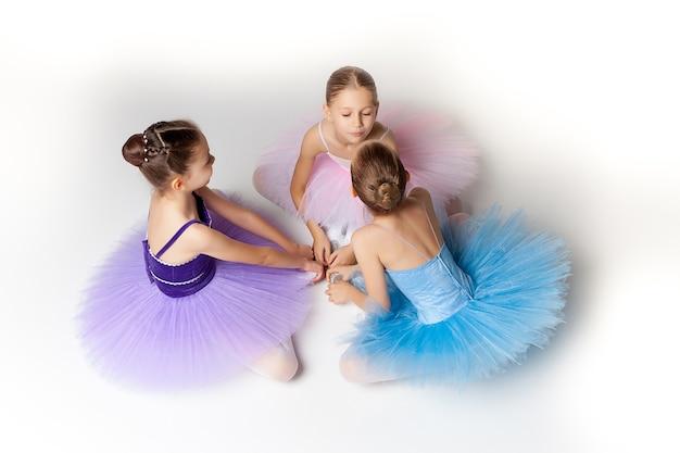 Три маленькие балетные девочки, сидящие в разноцветной пачке и пуантах вместе на белом фоне