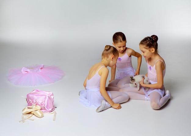 Три маленькие балетные девочки, сидящие в разноцветных пачках и пуантах вместе на белом фоне с кошкой
