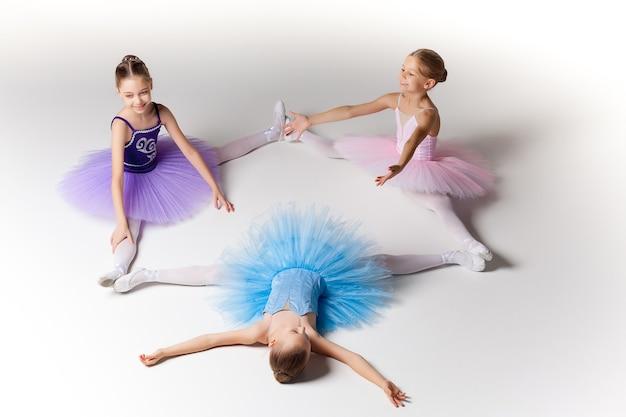Три маленькие балетные девочки сидят в балетной пачке и позируют вместе