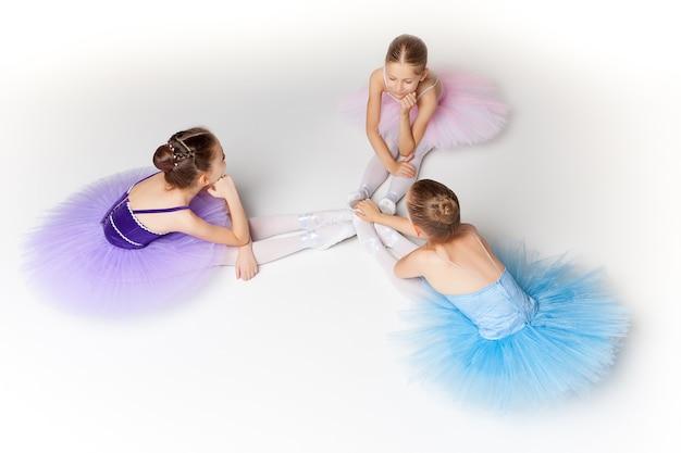 チュチュに座って一緒にポーズをとる3人の小さなバレエの女の子