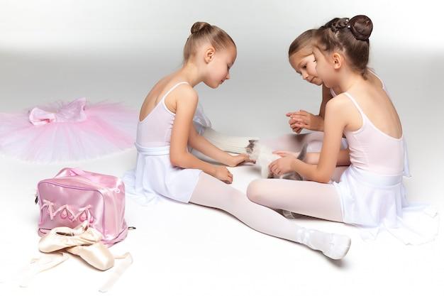 Tre bambine di balletto che si siedono insieme e che posano