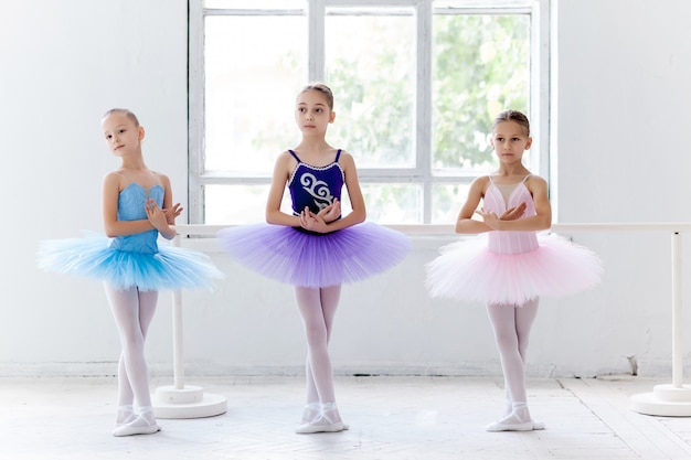 Three little ballet girls in tutu and posing together