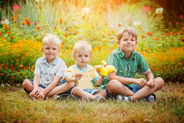 Three little brothers sitting on grass in sunny summer day.