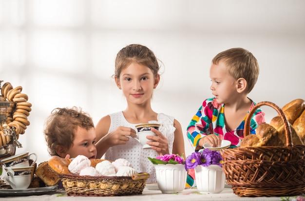 3人のかわいいロシアの子供がお茶を飲む