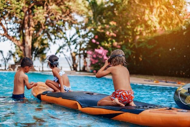 수영복을 입은 세 명의 작은 친구와 고글이 보트에서 수영하고 태국에서 휴가를 즐깁니다.