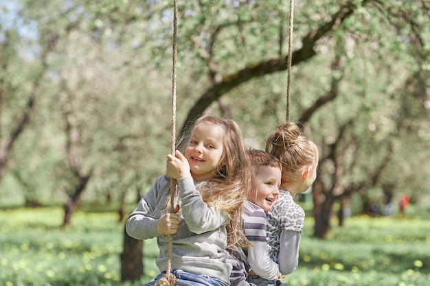Three little friends sitting on a swing in the garden on a spring day. the concept of a happy childhood