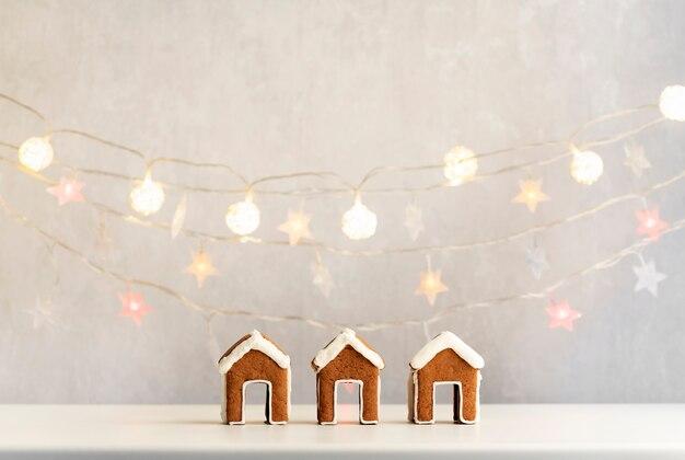 3つの小さなジンジャーブレッドハウスと背景のクリスマスライト。クリスマスのベーキング。