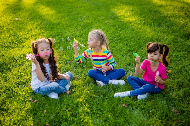 Three little girls of european, indian and asian ethnicity in the summer blow soap bubbles international children's day