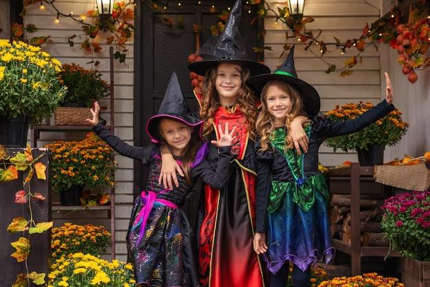 魔女の衣装を着た3人の少女がハロウィーンの楽しいパーティーを祝っています