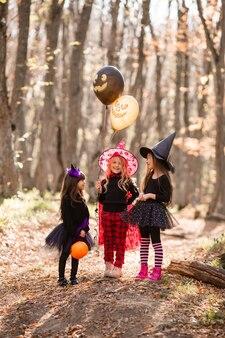 Три девчонки в костюмах ведьм от смеха гуляют по осеннему лесу с корзинами для сладостей