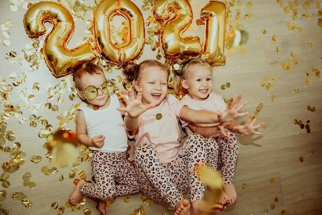 바닥에 누워있는 세 어린 소녀가 떨어지는 황금색 색종이를 기뻐합니다.
