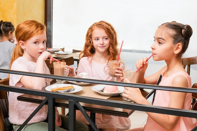 Three little girls sitting at a table in a cafe cheerfully drink hot chocolate and eat cakes