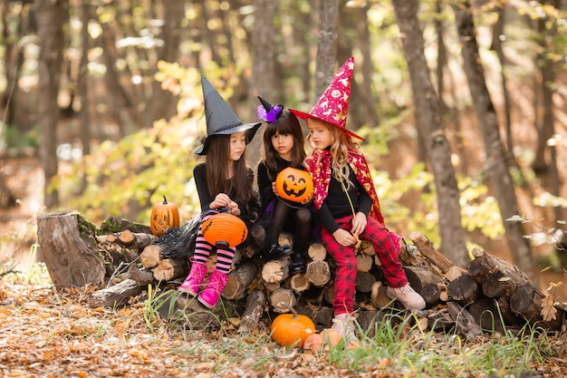 Three little girls in witch costumes laugh conjure walk through the autumn forest with baskets