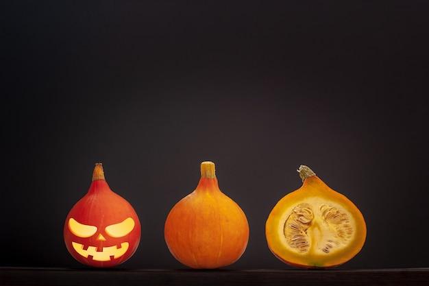 Три маленькие тыквы с лицом хэллоуина лежат в линию на сером фоне. одна тыква разрезанная с семечками внутри. красная тыква первая слева. скопируйте пространство. виньетка.