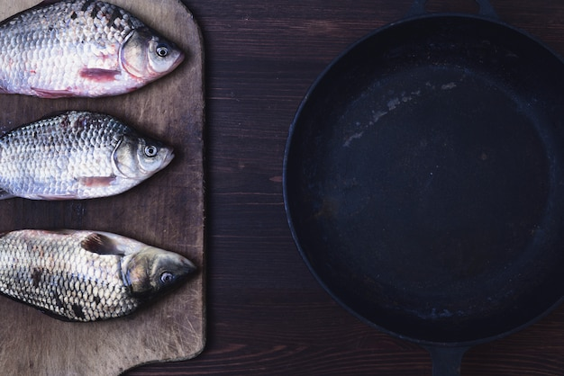 Three live carp fish in a scales on a kitchen board