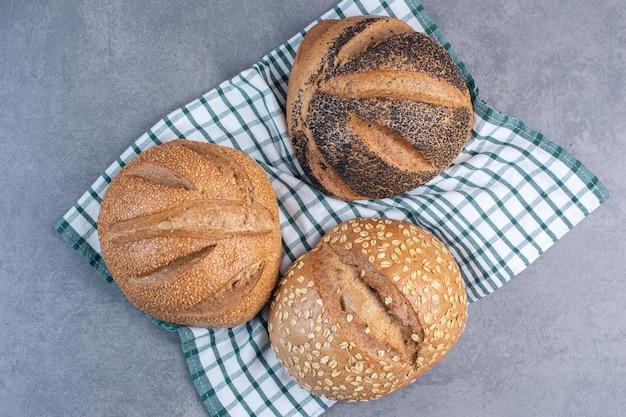 Tre pagnotte di pane con vari rivestimenti su un asciugamano su fondo marmo. foto di alta qualità