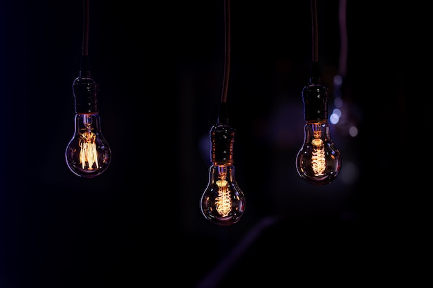 Three luminous lamps hang in the dark from the boke. decor and atmosphere concept.